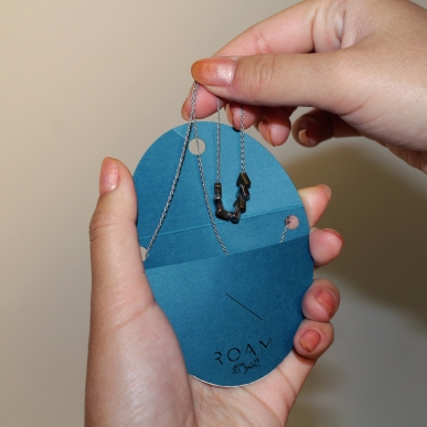 The hang tag for the necklace doubles as a travel case to keep the necklace untangled.